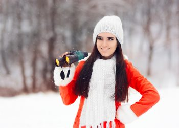 Smiling Winter Woman with Binoculars looking for Christmas
